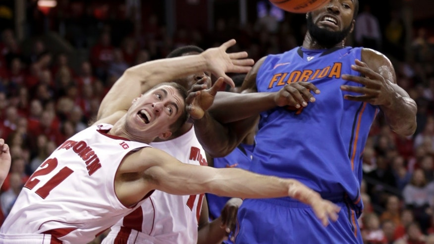 Wisconsin's Josh Gasser (21) and Nigel Hayes vie for a rebound with Florida's Patric Young during the first half of an NCAA college basketball game Tuesday, Nov. 12, 2013, in Madison, Wis. (AP Photo/Andy Manis)