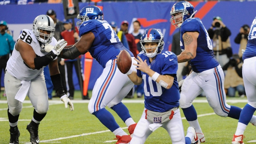 New York Giants quarterback Eli Manning (10) falls to his knees while trying to avoid being hit during the first half of an NFL football game against the Oakland Raiders, Sunday, Nov. 10, 2013, in East Rutherford, N.J. (AP Photo/Bill Kostroun)