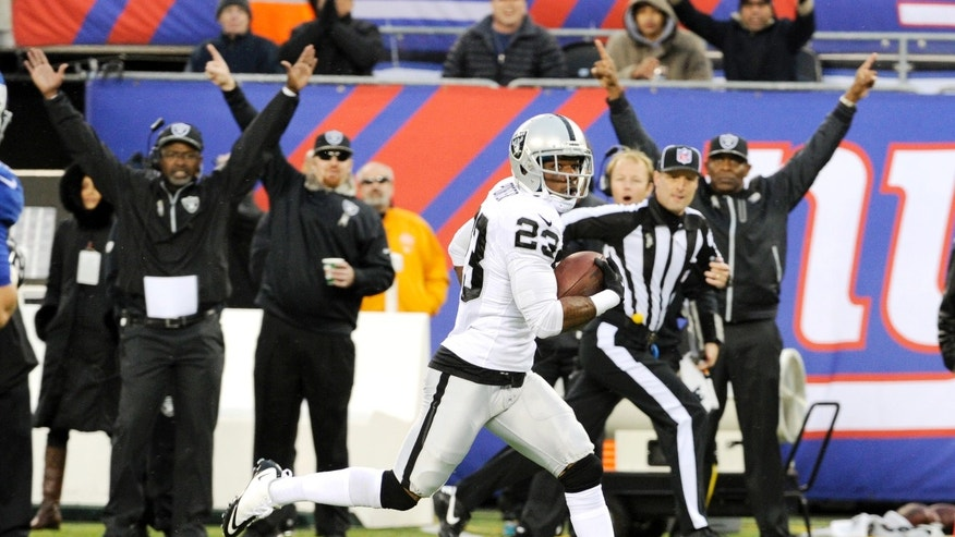 Oakland Raiders cornerback Tracy Porter (23) runs in a touchdown after intercepting a pass from New York Giants quarterback Eli Manning during the first half of an NFL football game on Sunday, Nov. 10, 2013, in East Rutherford, N.J. (AP Photo/Bill Kostroun)
