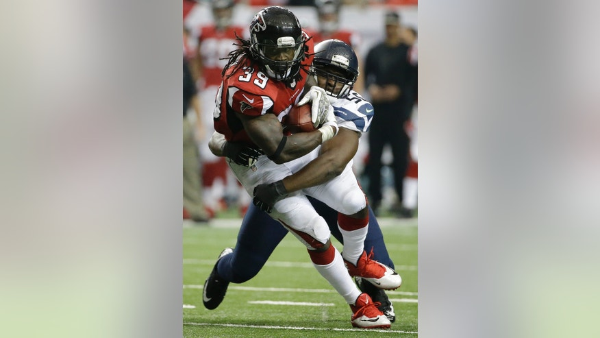 Seattle Seahawks defensive end Cliff Avril (56) wraps up Atlanta Falcons running back Steven Jackson (39) during the second half of an NFL football game, Sunday, Nov. 10, 2013, in Atlanta. (AP Photo/David Goldman)