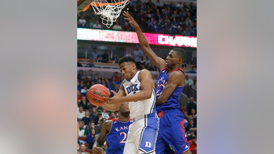 Duke forward Jabari Parker, left, grabs a rebound on a missed shot by Kansas guard Andrew Wiggins, right, during the second half of an NCAA college basketball game on Tuesday, Nov. 12, 2013, in Chicago. (AP Photo/Charles Rex Arbogast)