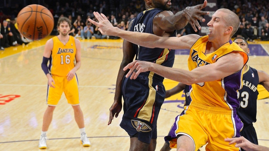 Los Angeles Lakers guard Steve Blake, right, passes the ball as New Orleans Pelicans guard Tyreke Evans, center, defends and Lakers center Pau Gasol watches during the first half of an NBA basketball game, Tuesday, Nov. 12, 2013, in Los Angeles. (AP Photo/Mark J. Terrill)