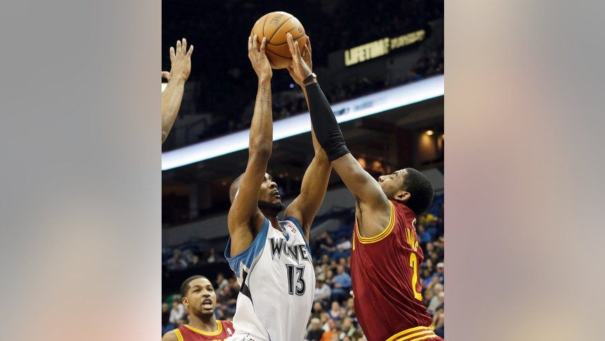 Minnesota Timberwolves' Corey Brewer, left, attempts a shot as Cleveland Cavaliers' Kyrie Irving tries to block it in the first quarter of an NBA basketball game Wednesday, Nov. 13, 2013, in Minneapolis. (AP Photo/Jim Mone)