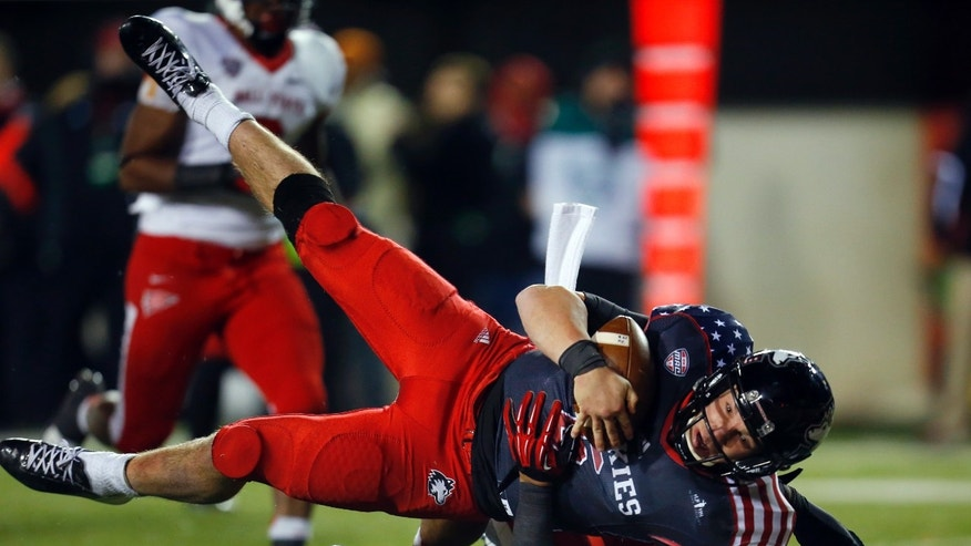 Northern Illinois quarterback Jordan Lynch, left, runs over Ball State safety Dae'Shaun Hurley for a 16-yard touchdown during the second half of an NCAA college football game Wednesday, Nov. 13, 2013, in DeKalb, Ill. Northern Illinois won 48-27. (AP Photo/Jeff Haynes)