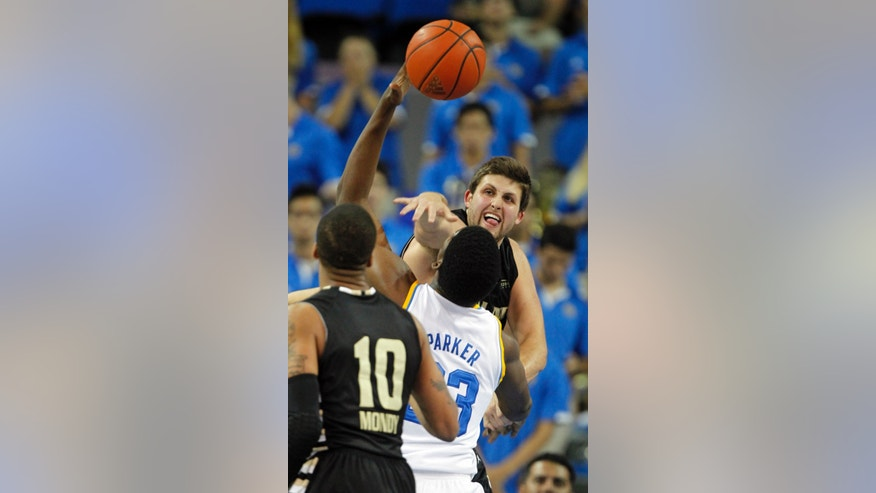 Oakland center Corey Petros, top, blocks a shot by UCLA center Tony Parker, center, with Oakland guard Duke Mondy (10) defending in the first half of an NCAA college basketball game Tuesday, Nov. 12, 2013, in Los Angeles. (AP Photo/Alex Gallardo)