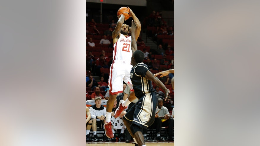 Oklahoma's Cameron Clark (21) shoots over Idaho's Bira Seck during an NCAA college basketball game in Norman, Okla., Wednesday, Nov. 13, 2013.  (AP Photo/The Oklahoman, Bryan Terry) LOCAL TV OUT (KFOR,KOCO,KWTV,KOKH, KAUT OUT); LOCAL INTERNET OUT; LOCAL PRINT OUT (EDMOND SUN, NORMAN TRANSCRIPT, OKLAHOMA GAZETTE, SHAWNEE NEWS-STAR THE JOURNAL RECORD OUT); TABLOIDS OUT