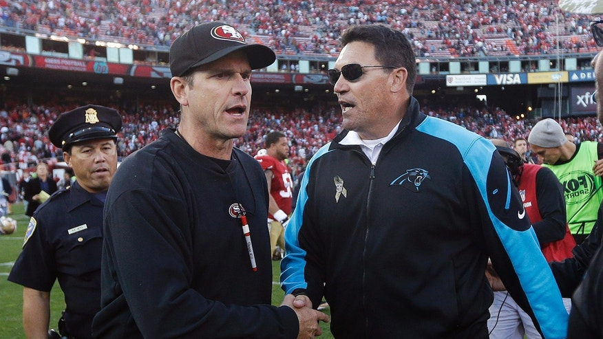 San Francisco 49ers head coach Jim Harbaugh, left, shakes hands with Carolina Panthers head coach Ron Rivera after an NFL football game in San Francisco, Sunday, Nov. 10, 2013. (AP Photo/Marcio Jose Sanchez)