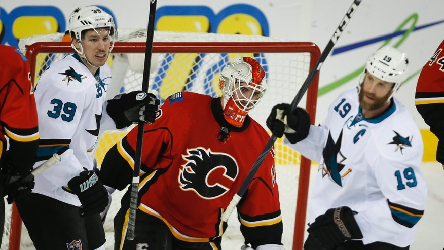 San Jose Sharks' Logan Couture, left, and Joe Thornton, right, celebrate their team's goal as Calgary Flames goalie Reto Berra, from Switzerland, gets up during the first period of an NHL hockey game Tuesday, Nov. 12, 2013, in Calgary, Alberta. (AP Photo/The Canadian Press, Jeff McIntosh)