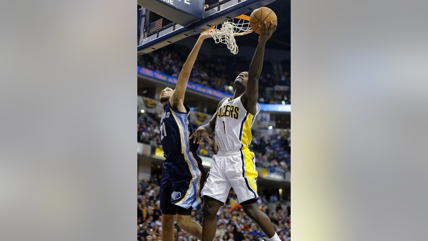 Indiana Pacers guard Lance Stephenson, right, gets a bucket on a shot under Memphis Grizzlies forward Tayshaun Prince in the second half of an NBA basketball game in Indianapolis, Monday, Nov. 11, 2013. The Pacers defeated the Grizzlies 95-79.  Stephenson had his first triple-double of his career with 13 points, 11, rebounds and 12 assists. (AP Photo/Michael Conroy)