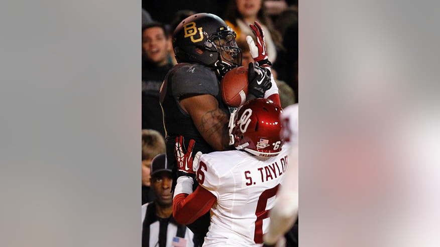 Baylor Bears wide receiver Antwan Goodley (5) pulls in a fourth quarter touchdown while being covered in the end zone by Oklahoma Sooners defensive back Stanvon Taylor (6) at Floyd Casey Stadium in Waco, Thursday, Nov. 7, 2013. Baylor won 41-12. (AP Photo/The Dallas Morning News, Tom Fox)
