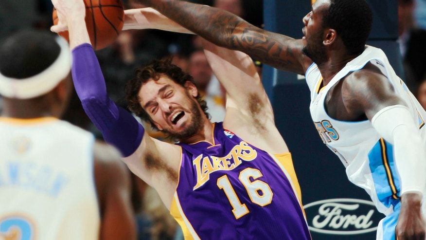 Los Angeles Lakers center Pau Gasol (16), of Spain, pulls in a rebound as Denver Nuggets forward Jordan Hamilton covers in the first quarter of an NBA basketball game in Denver on Wednesday, Nov. 13, 2013. (AP Photo/David Zalubowski)