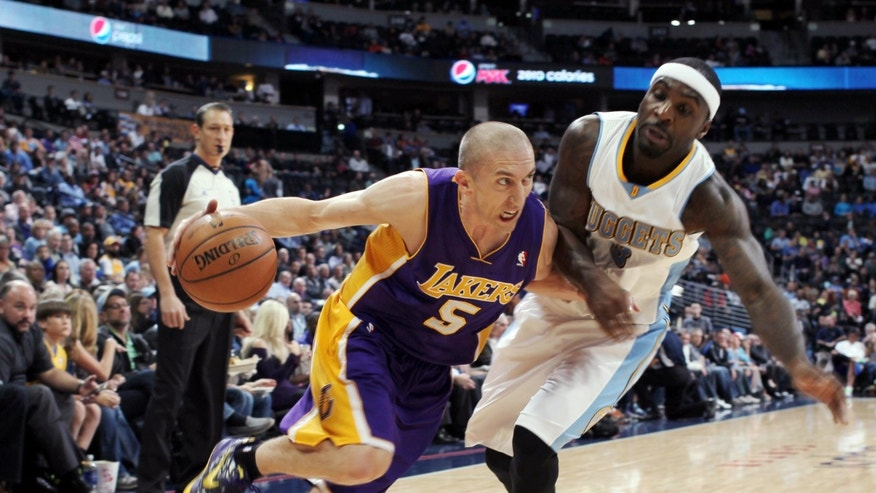Los Angeles Lakers guard Steve Blake, left, works the ball inside past Denver Nuggets guard Ty Lawson in the first quarter of an NBA basketball game in Denver on Wednesday, Nov. 13, 2013. (AP Photo/David Zalubowski)