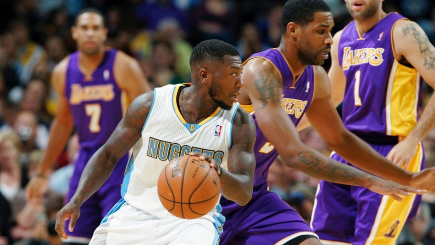 Denver Nuggets guard Nate Robinson, front, picks up a loose ball as Los Angeles Lakers forward Shawne Williams covers in the first quarter of an NBA basketball game in Denver on Wednesday, Nov. 13, 2013. (AP Photo/David Zalubowski)