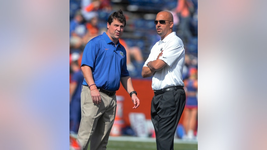 Florida coach Will Muschamp, left and Vanderbilt coach James Franklin, right, watch their teams warmup as the two met together before during the first half of an NCAA college football game Saturday, Nov. 9, 2013 in Gainesville, Fla.  (AP Photo/Phil Sandlin)