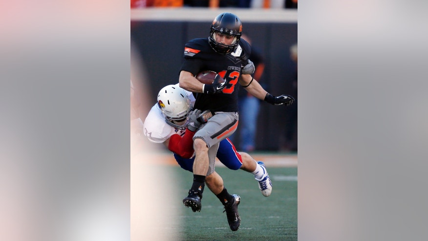 Oklahoma State wide receiver David Glidden (13) is tackled by Kansas defender Ben Heeney (31) in the first quarter of an NCAA college football game in Stillwater, Okla., Saturday, Nov. 9, 2013. (AP Photo/Sue Ogrocki)
