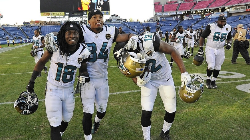 Jacksonville Jaguars players Ace Sanders (18), Cecil Shorts (84) and Mike Brown (12) celebrate as they leave the field after the Jaguars beat the Tennessee Titans 29-27 in an NFL football game on Sunday, Nov. 10, 2013, in Nashville, Tenn. (AP Photo/Mark Zaleski)