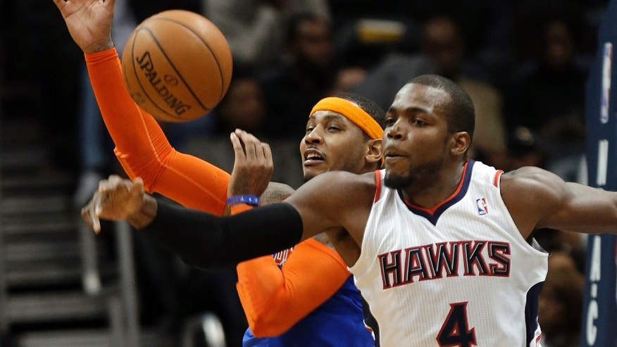 New York Knicks forward Carmelo Anthony (7) and Atlanta Hawks forward Paul Millsap (4) vie for a rebound in the first half of an NBA basketball game Wednesday, Nov. 13, 2013, in Atlanta. (AP Photo/John Bazemore)