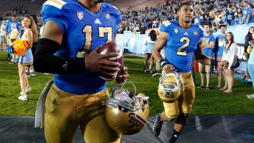 FILE - In this Nov. 2, 2013 file photo, UCLA quarterback Brett Hundley, left, runs off the field with quarterback Asiantii Woulard (2) after defeating Colorado 45-23 in an NCAA college football game in Pasadena, Calif. Hundley is grateful No. 13 UCLA still controls its destiny in the Pac-12 South title race, but he realizes the Bruins probably must outscore high-flying Washington to get there on Friday night at the Rose Bowl. (AP Photo/Alex Gallardo, File)