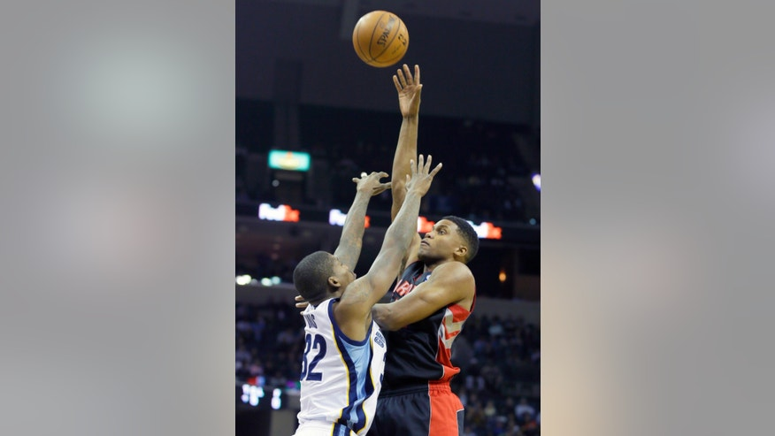 Toronto Raptors' Rudy Gay, right, shoots over Memphis Grizzlies' Ed Davis in the first half of an NBA basketball game in Memphis, Tenn., Wednesday, Nov. 13, 2013. (AP Photo/Danny Johnston)