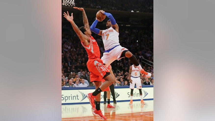 New York Knicks' Carmelo Anthony (7) shoots over Houston Rockets' Greg Smith during the first half of an NBA basketball game Thursday, Nov. 14, 2013, in New York. Smith was hurt on the play. (AP Photo/Frank Franklin II)