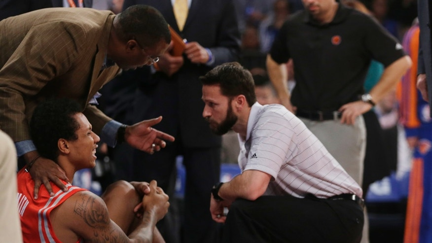 Trainers check on Houston Rockets' Greg Smith (4) after he was injured during the first half of an NBA basketball game against the New York Knicks on Thursday, Nov. 14, 2013, in New York. (AP Photo/Frank Franklin II)