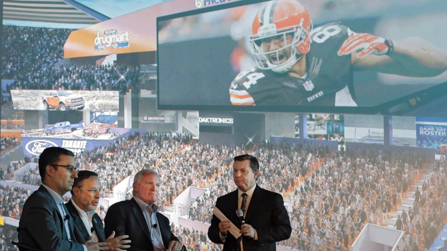 Cleveland Browns CEO Joe Banner, second from left, speaks during a presentation on a proposed renovation to FirstEnegy Stadium with team president Alec Scheiner, left, owner Jimmy Haslam and emcee Jim Donovan, right, Wednesday, Nov. 13, 2013, in Cleveland. The two-year modernization project, proposed for completion during the next two off-seasons, would include two new video boards nearly triple the size of the boards currently in each end zone and increasing the lower bowl's seating capacity while improving sight-lines. (AP Photo/Mark Duncan)