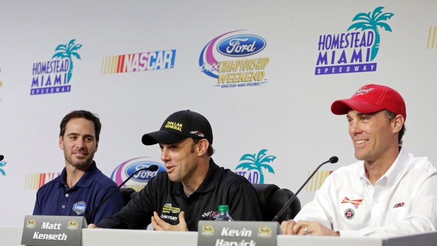 NASCAR driver Matt Kenseth, center, answers a question as Jimmie Johnson, left, and Kevin Harvick, right, smile during a news conference Thursday, Nov. 14, 2013 at the Homestead-Miami Speedway in Homestead, Fla. Johnson, Kenseth, and Kevin Harvick will be competing in Sunday's NASCAR Sprint Cup series race. (AP Photo/Alan Diaz)