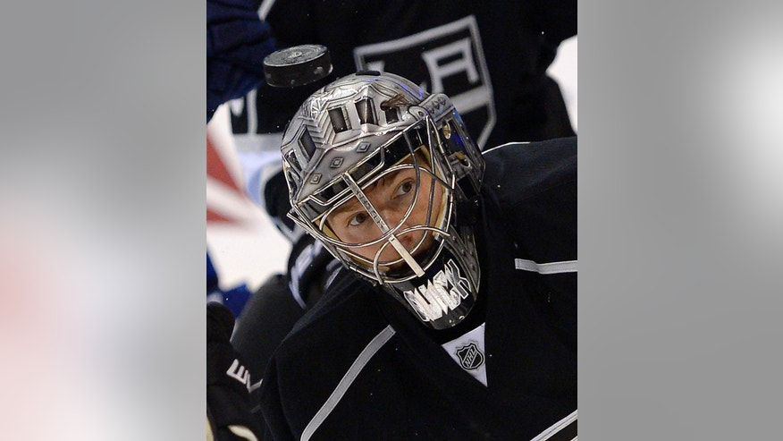A puck flies in front of Los Angeles Kings goalie Jonathan Quick during the first period of an NHL hockey game against the Vancouver Canucks, Saturday, Nov. 9, 2013, in Los Angeles.  (AP Photo/Mark J. Terrill)