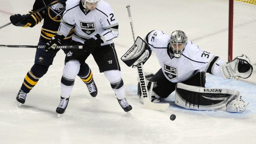 Buffalo Sabres center Brian Flynn (65) battles for a rebound as Los Angeles Kings defenseman Slava Voynov, center, of Russia, and goaltender Jonathan Quick (32) defends during the third period of an NHL hockey game in Buffalo, N.Y., Tuesday, Nov. 12, 2013. Buffalo won 3-2. (AP Photo/Gary Wiepert)