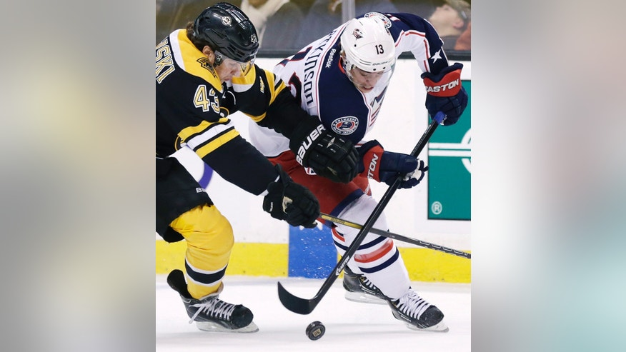 Columbus Blue Jackets right wing Cam Atkinson, right, pushes the puck ahead as he is pressured by Boston Bruins defenseman Matt Bartkowski (43) during the first period of an NHL hockey game, in Boston, Thursday, Nov. 14, 2013. (AP Photo/Charles Krupa)