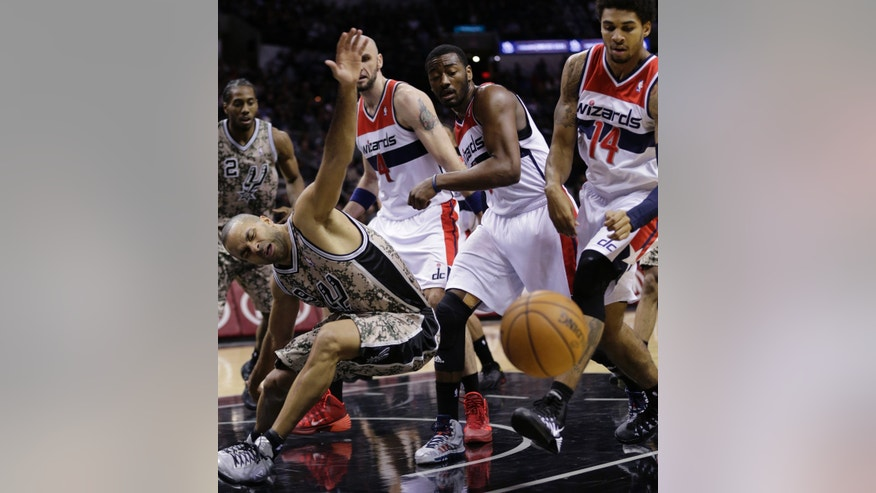 San Antonio Spurs' Tony Parker (9), of France, loses control of the ball as he is pressured by Washington Wizards' Marcin Gortat (4), John Wall, second from right, and Glen Rice (14) during the first half of an NBA basketball game on Wednesday, Nov. 13, 2013, in San Antonio. (AP Photo/Eric Gay)