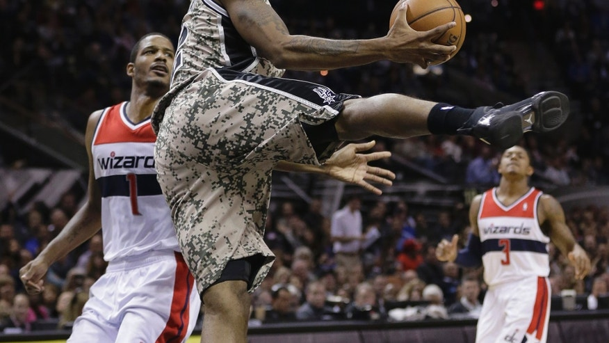 San Antonio Spurs' Kawhi Leonard, center, shoots off-balance as he is fouled by Washington Wizards' Trevor Ariza, left, during the first half of an NBA basketball game on Wednesday, Nov. 13, 2013, in San Antonio. (AP Photo/Eric Gay)