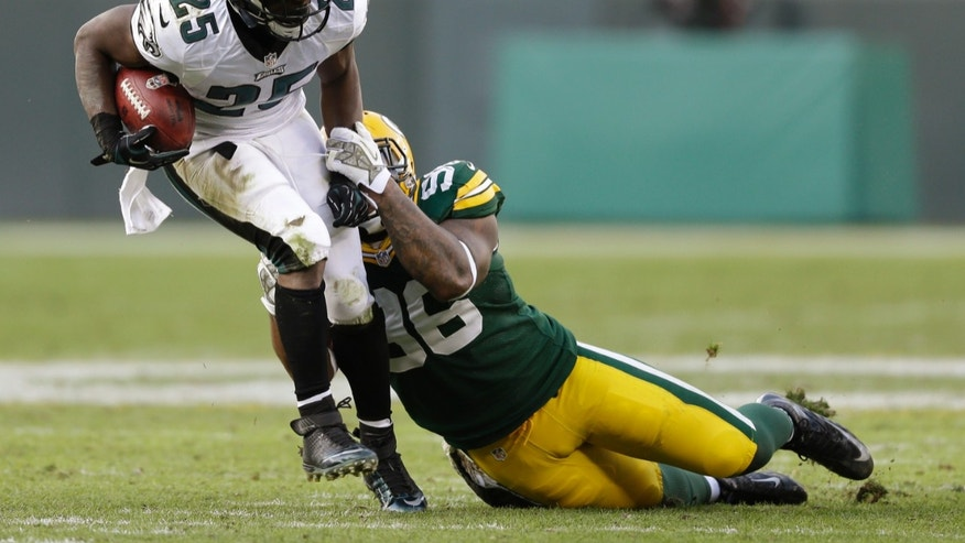 Philadelphia Eagles' LeSean McCoy tries to run past Green Bay Packers' Mike Neal during the second half of an NFL football game Sunday, Nov. 10, 2013, in Green Bay, Wis. The Eagles won 27-13. (AP Photo/Tom Lynn)