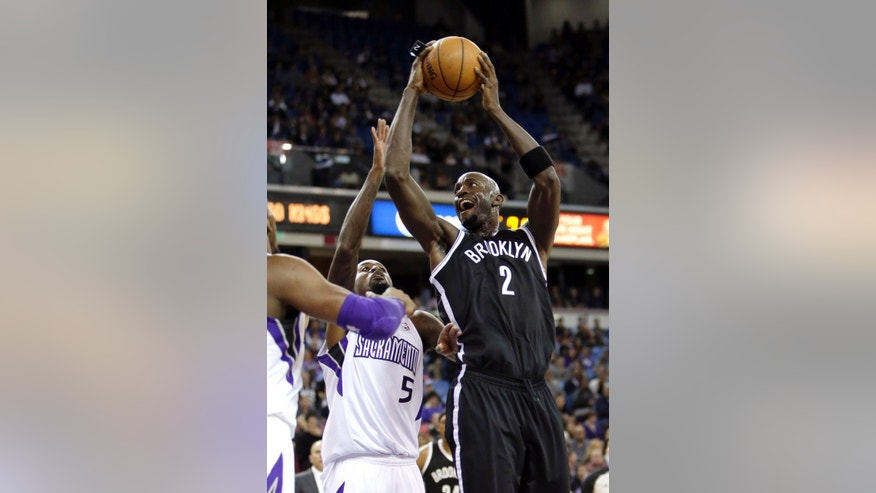 Brooklyn Nets forward Kevin Garnett, right, goes to the basket against Sacramento Kings forward John Salmons, during the first quarter of an NBA basketball game in Sacramento, Calif., Wednesday, Nov. 13, 2013. (AP Photo/Rich Pedroncelli)