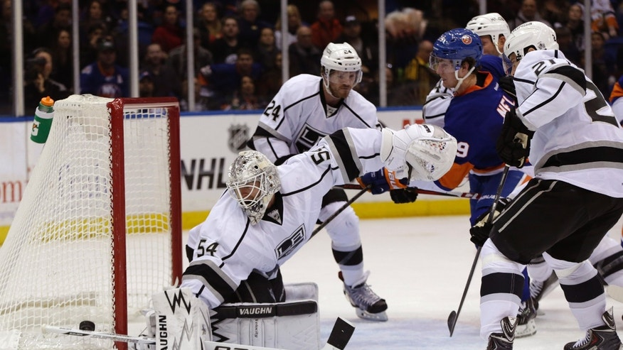 Los Angeles Kings goalie Ben Scrivens (54) turns away a shot as New York Islanders forward Brock Nelson (29) fends off Kings defenders in the second period of an NHL hockey game at Nassau Coliseum in Uniondale, N.Y., Thursday, Nov. 14, 2013. (AP Photo/Kathy Willens)