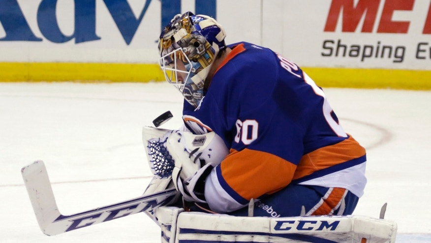 New York Islanders goalie Kevin Poulin makes a save in the first period of an NHL hockey game against the Los Angeles Kings at Nassau Coliseum in Uniondale, N.Y., Thursday, Nov. 14, 2013. (AP Photo/Kathy Willens)