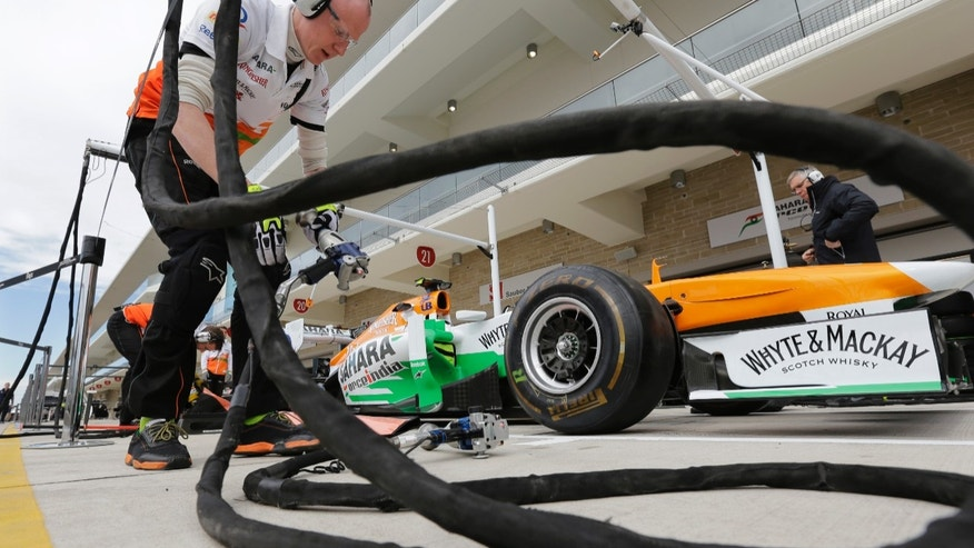 A crew member works on Force India driver Adrian Sutil of Germany's car in preparation for the Formula One U.S. Grand Prix auto race at the Circuit of the Americas, Thursday, Nov. 14, 2013, in Austin, Texas. (AP Photo/Eric Gay)