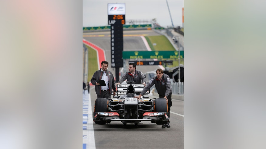 Crew members push Sauber driver Nico Hulkenberg of Germany's car to the pits in preparation for the Formula One U.S. Grand Prix auto race at the Circuit of the Americas, Thursday, Nov. 14, 2013, in Austin, Texas. (AP Photo/David J. Phillip)