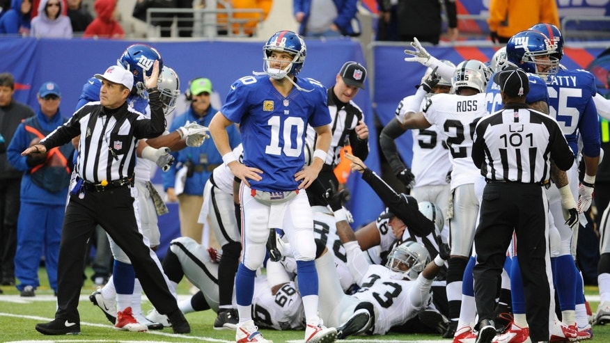 New York Giants quarterback Eli Manning (10) walks away as an official, left, signals for the ball in favor of the Oakland Raiders after a Giants turnover during the first half of an NFL football game on Sunday, Nov. 10, 2013, in East Rutherford, N.J. (AP Photo/Bill Kostroun)