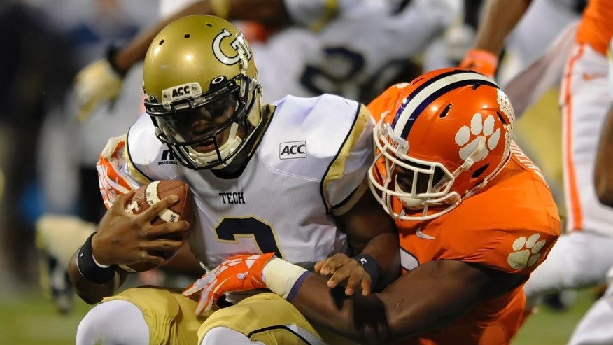 Gergia Tech quarterback Vad Lee, left, is sacked by Clemson's Corey Crawford during the first half of an NCAA college football game Thursday, Nov.14, 2013, in Clemson, S.C. (AP Photo/ Richard Shiro)