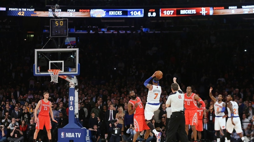 New York Knicks' Carmelo Anthony (7) shoots over Houston Rockets' James Harden (13) during the second half of an NBA basketball game Thursday, Nov. 14, 2013, in New York. The Rockets won 109-106. Harden fouled Anthony on the play. (AP Photo/Frank Franklin II)