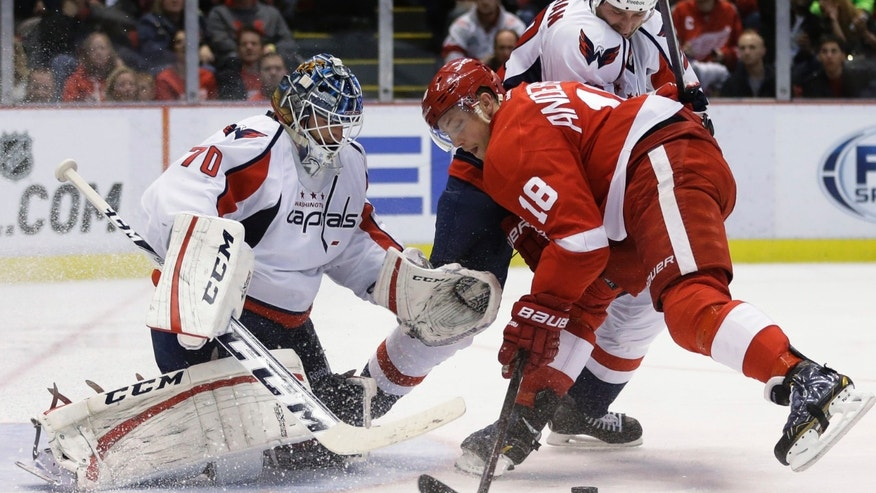 Detroit Red Wings center Joakim Andersson (18), of Sweden, tries controlling the puck in front of Washington Capitals goalie Braden Holtby (70) during the second period of an NHL hockey game in Detroit, Friday, Nov. 15, 2013. (AP Photo/Carlos Osorio)