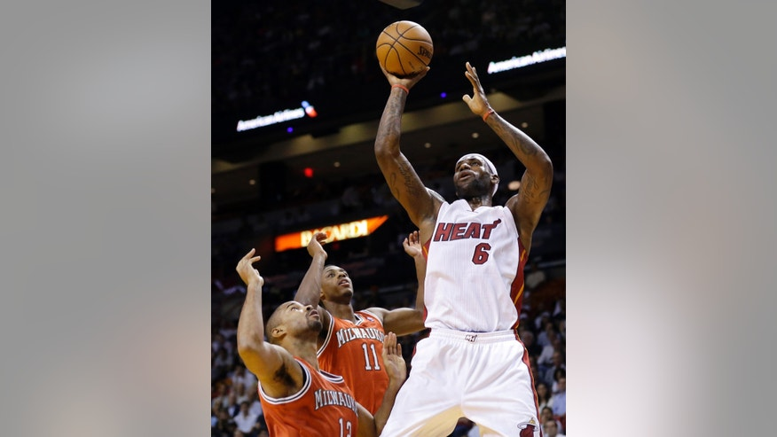 Miami Heat's LeBron James (6) shoots over Milwaukee Bucks' Gary Neal, left, and Brandon Knight (11) during the first half of an NBA basketball game Tuesday, Nov. 12, 2013, in Miami. (AP Photo/Lynne Sladky)