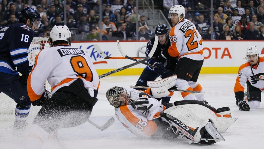 Philadelphia Flyers goaltender Steve Mason (35) stops a shot from Winnipeg Jets' Andrew Ladd (16) as Jets' Bryan Little (18) and Flyers' Erik Gustafsson (26) look for the rebound during second-period NHL hockey game action in Winnipeg , Manitoba, Friday, Nov. 15, 2013. (AP Photo/The Canadian Press, John Woods)