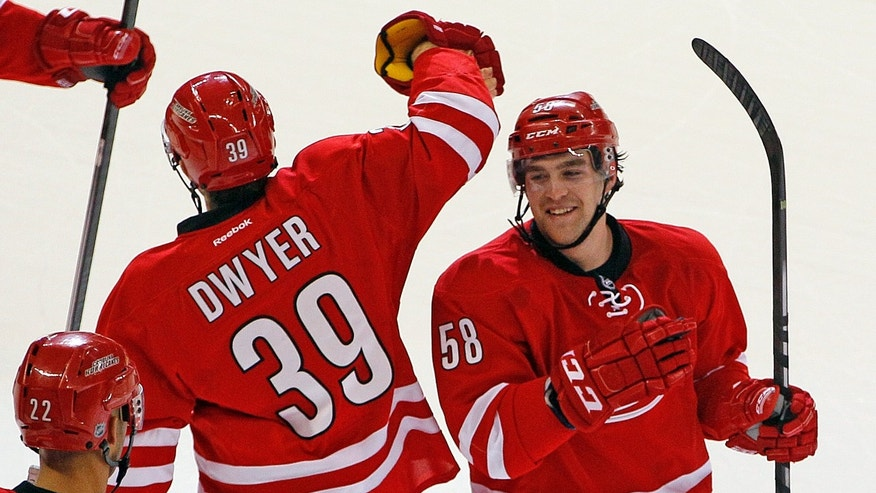 Carolina Hurricanes' Chris Terry (58) is congratulated by teammate Patrick Dwyer (39) on Terry's game-winning shootout goal against the Anaheim Ducks in Raleigh, N.C., Friday, Nov. 15, 2013. (AP Photo/Karl B DeBlaker)