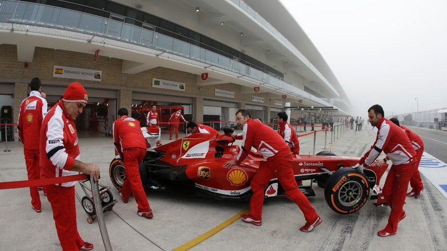 Pit crews push Ferrari driver Fernando Alonso of Spain's car to their garage before the first practice session for the Formula One U.S. Grand Prix auto race at the Circuit of the Americas, Friday, Nov. 15, 2013, in Austin, Texas. (AP Photo/Darron Cummings)