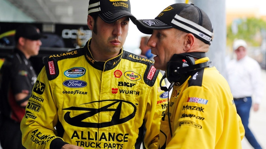 Driver Sam Hornish Jr., left, talks to a member of his crew during practice for Saturday's NASCAR Nationwide series auto race, Friday, Nov. 15, 2013, in Homestead, Fla. (Terry Renna)
