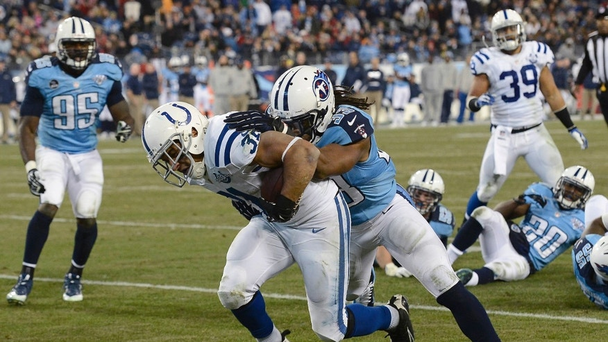 Indianapolis Colts running back Donald Brown (31) scores a touchdown on a 6-yard run as Tennessee Titans safety Michael Griffin (33) tries to bring him down in the third quarter of an NFL football game Thursday, Nov. 14, 2013, in Nashville, Tenn. (AP Photo/Mark Zaleski)