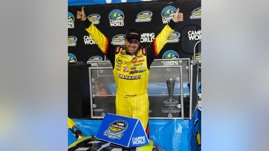 Matt Crafton celebrates his series title in NASCAR Trucks, after the auto race at Homestead-Miami Speedway in Homestead, Fla., Friday, Nov. 15, 2013. (AP Photo/Terry Renna)