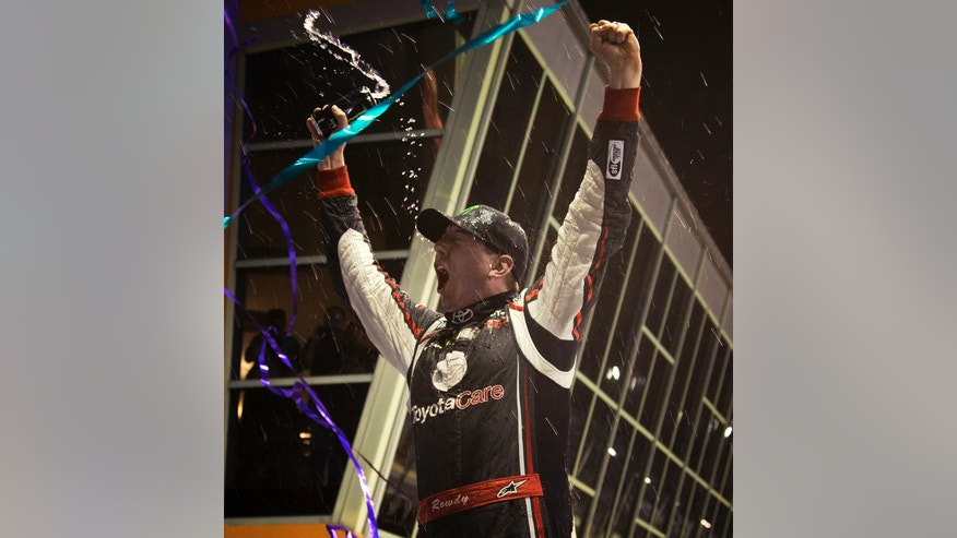 Kyle Busch celebrates after winning the NASCAR Trucks auto race, at Homestead-Miami Speedway in Homestead, Fla., Friday, Nov. 15, 2013. (AP Photo/J Pat Carter)